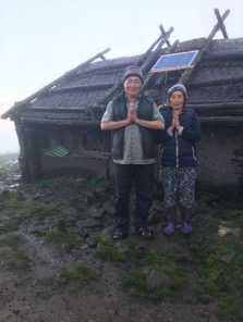 A Tibetan nomad couple outside their home with their new solar panel which provides lighting indoors